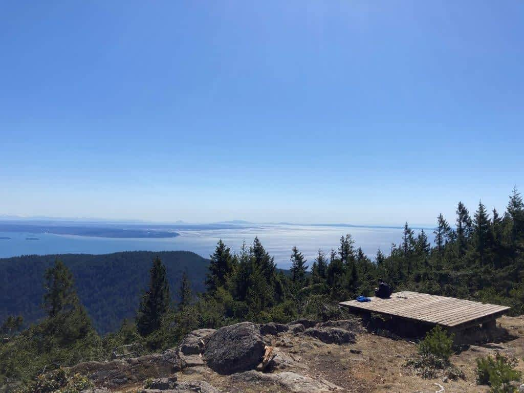 Woman sitting on the helicopter pad enjoying the view from the top of Mount Gardner - a Bowen Island hike