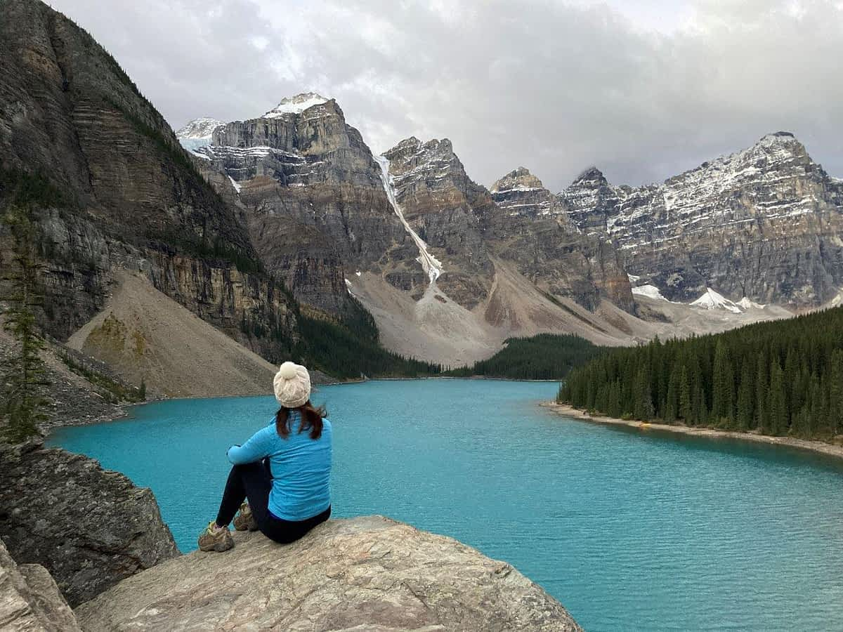Girl sitting on rock in front of lake with 10 mountain peaks behind