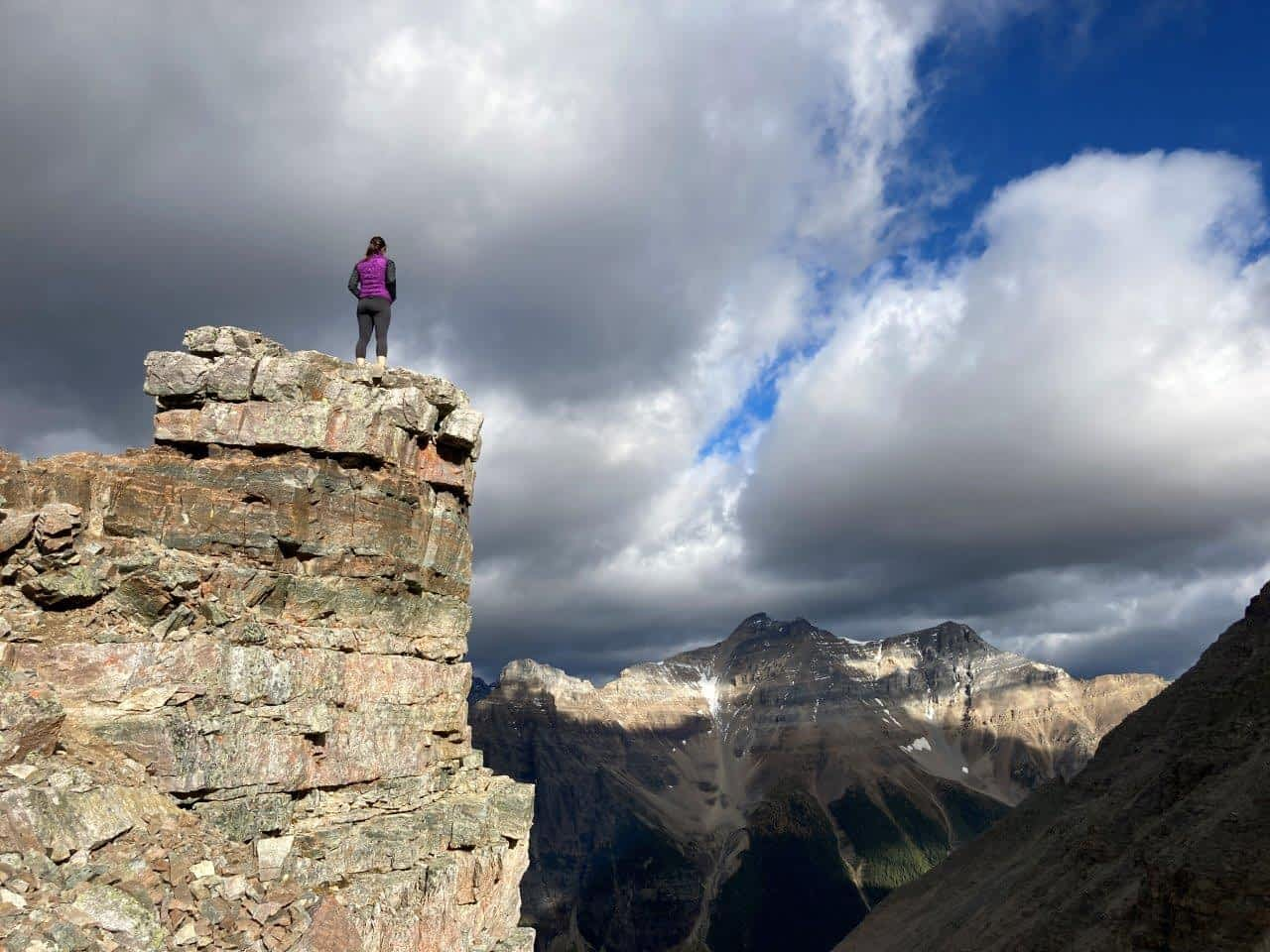 Girl on rock outcropping and mountains in the background
