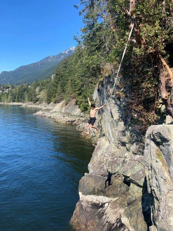 Man mid leap at the Lions Bay Cliff Jumping spot with cliffs behind and water below