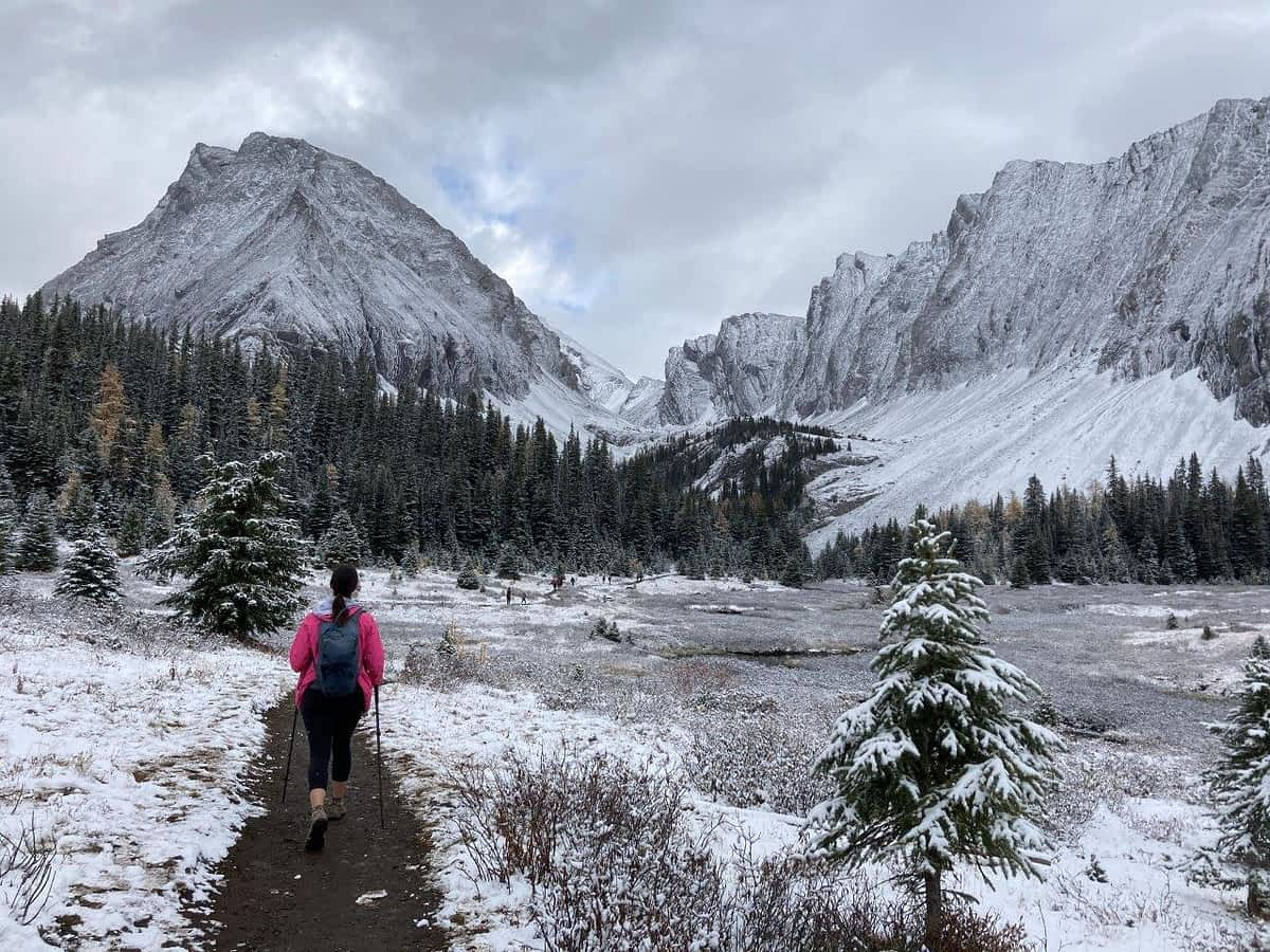 Girl walking on trail surrounded by snowy mountains on one of the best easy hikes Canmore offers