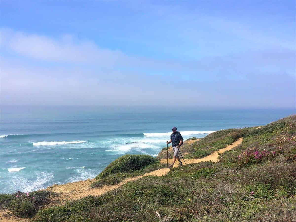 Man hiking on sandy trail on cliffs above ocean