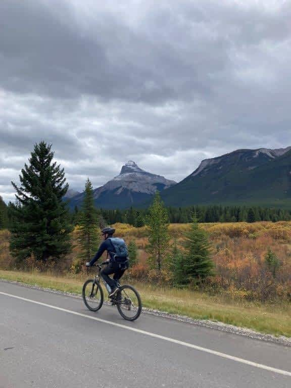 Man biking on Bow Valley Parkway with mountains in the background