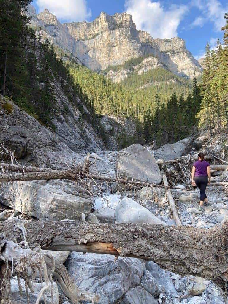 Girl walking up a rocky canyon on one of the best easy hikes Canmore offers